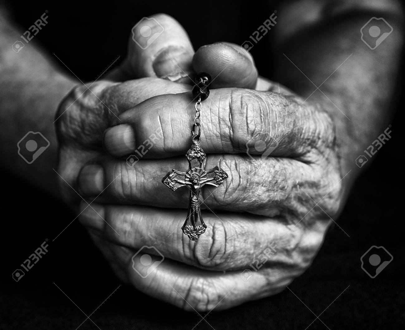 Rosary in old closed hands together black and white fotography stock photo 72969393