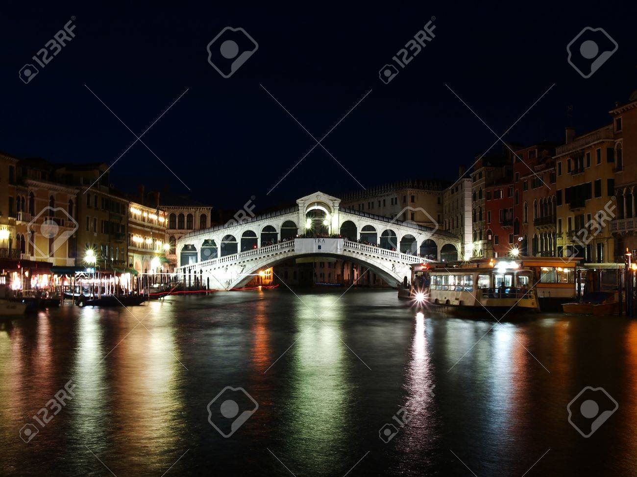 VENICE, ITALY - JULY 02: Tourist enjoy day and night on the Rialto Bridge on July 02, 2011 in Venice, Italy. Originally built out of wood and having collapsed, in 1591 was completed out of stone.  Stock Photo - 12790056