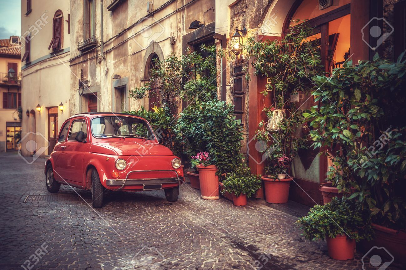 Old vintage cult car parked on the street by the restaurant, in the Italian town. - 33479685
