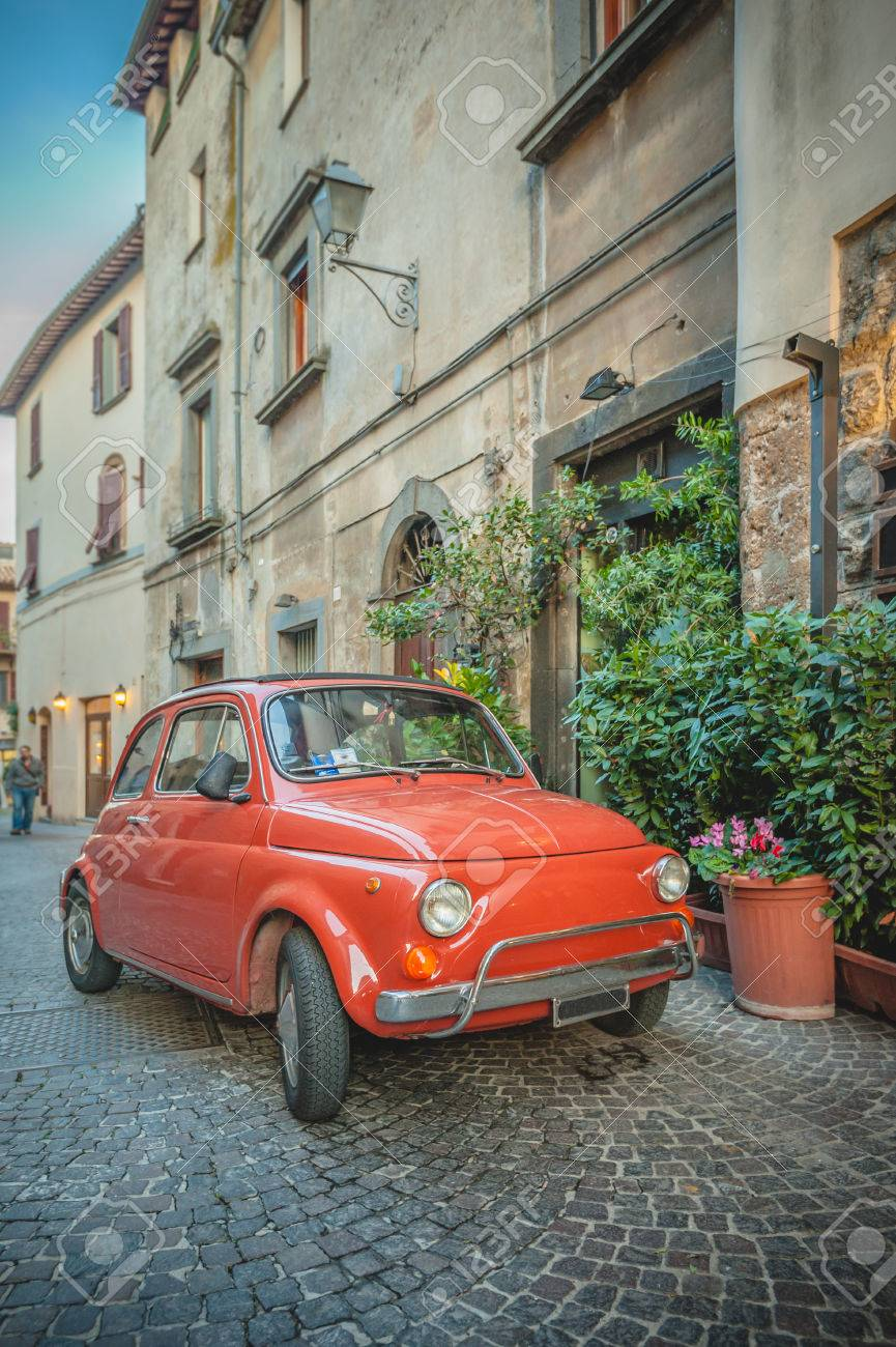 Old vintage cult car parked on the street by the restaurant, in the Italian town. - 33479699