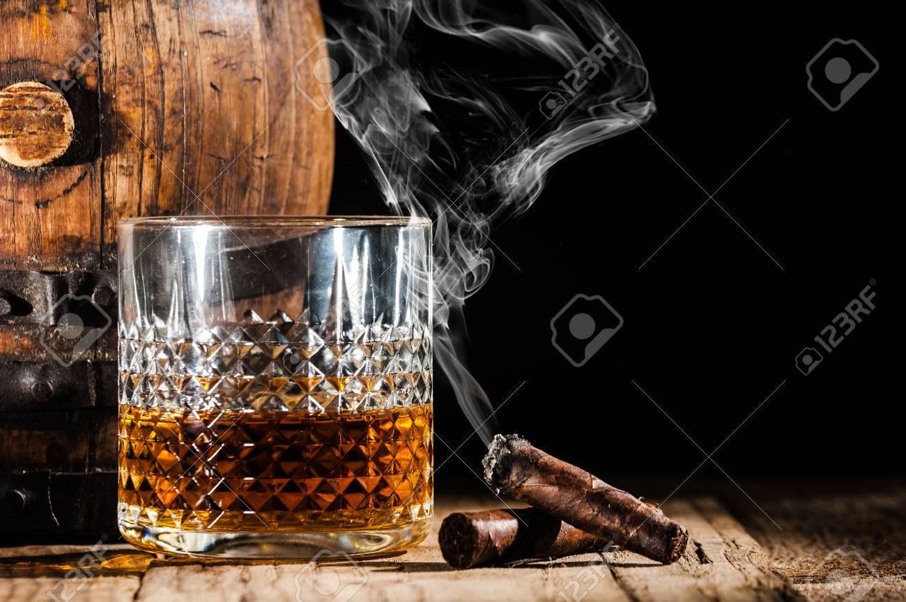 Glass of alcohol and smoking noble cigar on a black background - 34912397
