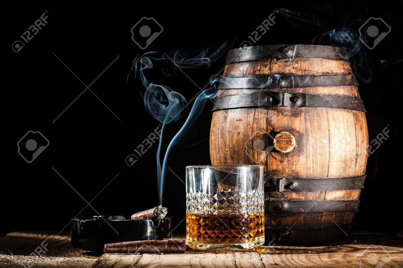 Glass of alcohol and smoking noble cigar on a black background - 34912398