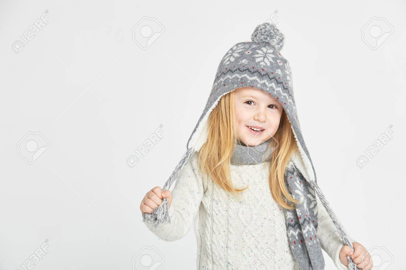 Beautiful blond girl playing in the winter warm hat and scarf on a white background - 35020712