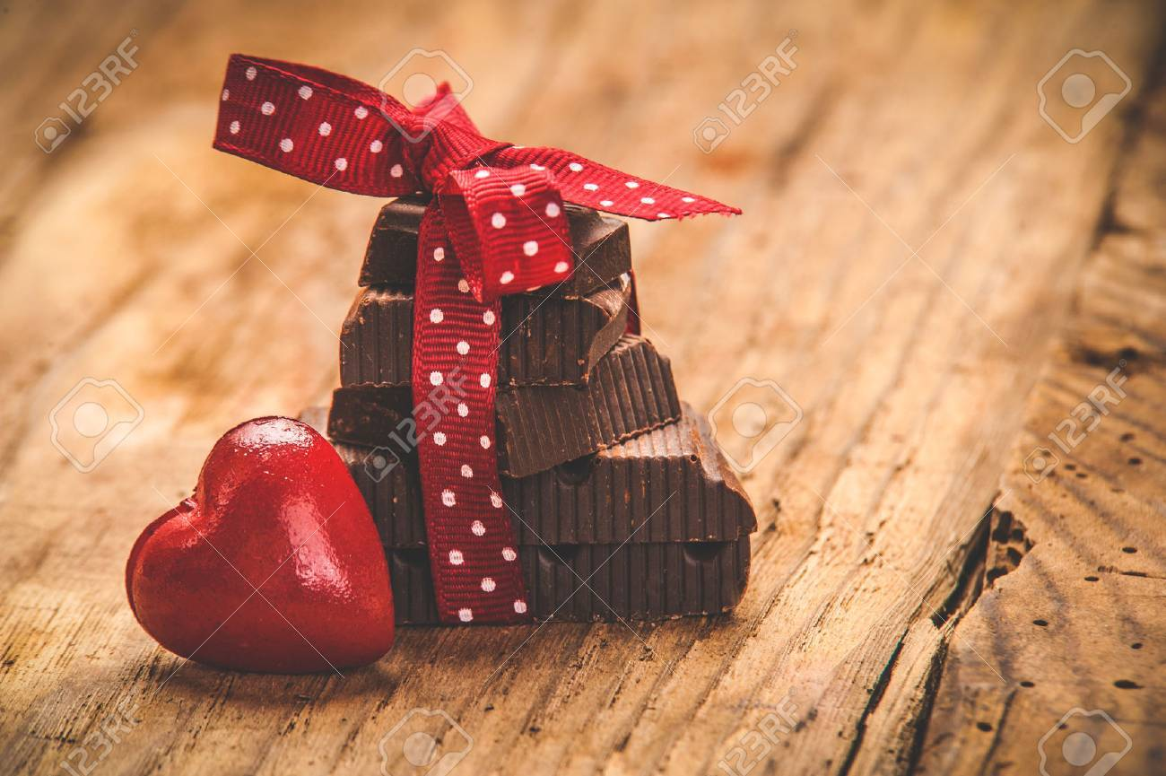 Chocolate with ribbon and heart on St. Valentine - 35382301