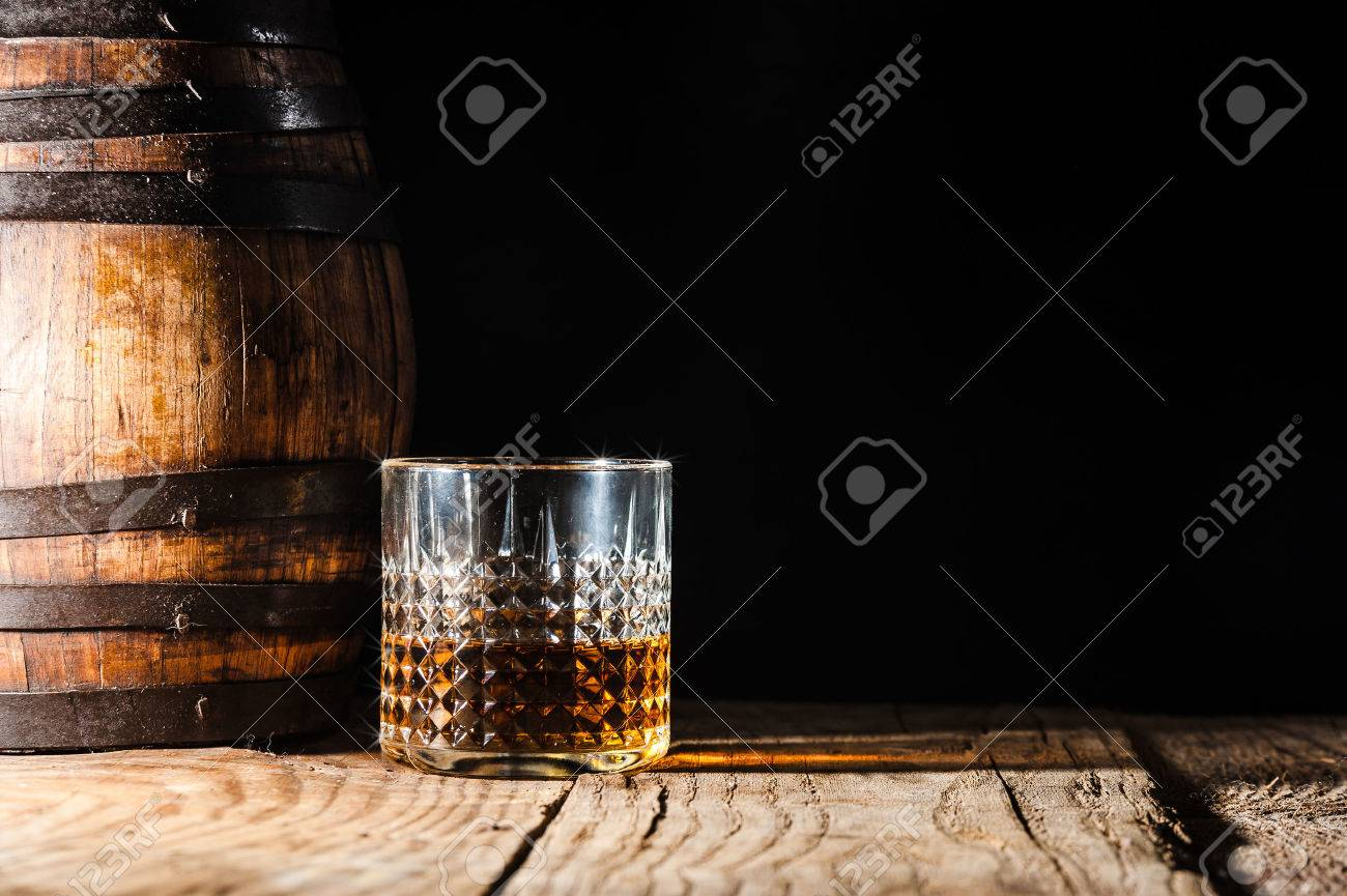 Strong alcohol on a wooden table and barrel - 36352128