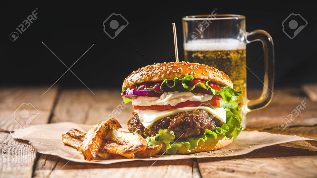 Fresh and juicy hamburger on a paper pad with a beer on a wooden table. - 37882379