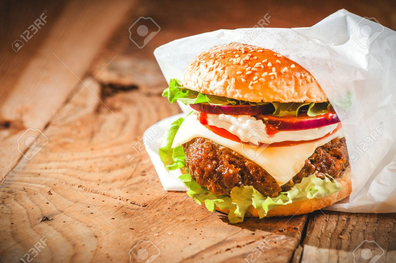 Tasty hamburger with fast food in a white paper on the wooden table. - 37882381