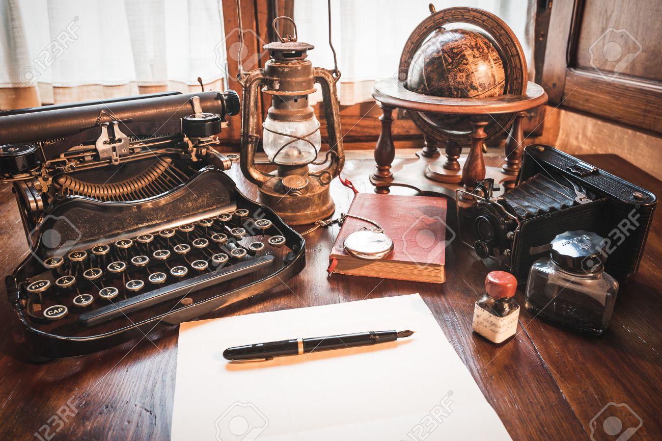 Vintage items, camera, pen, globe, clock, typewriter on the old desk - 38017710
