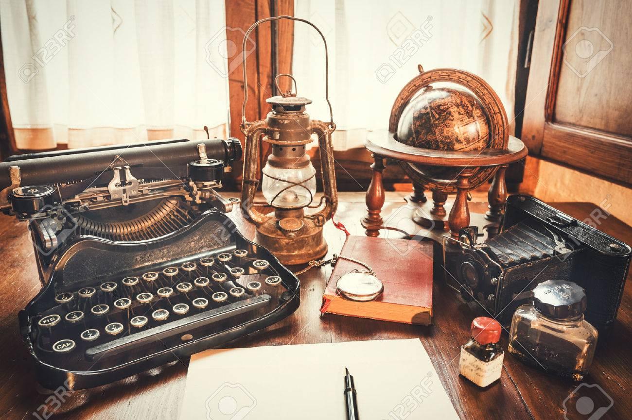 Vintage items, camera, pen, globe, clock, typewriter on the old desk - 42814256
