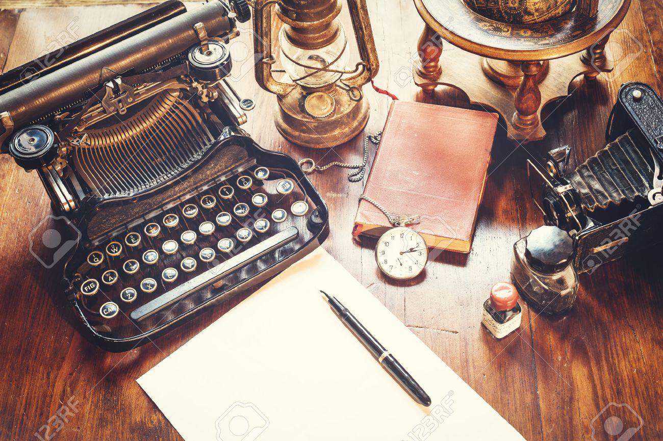 Vintage items, camera, pen, globe, clock, typewriter on the old desk - 44027866