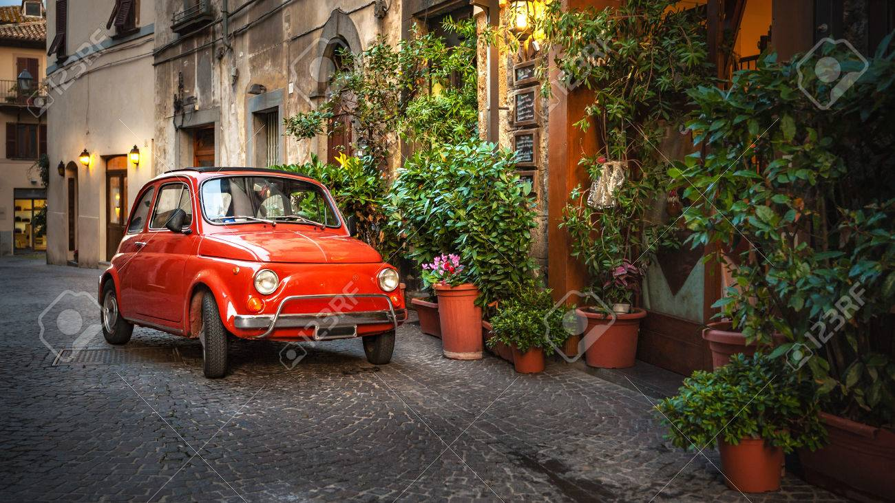 Old vintage cult car parked on the street by the restaurant, in Italian village. - 46114971