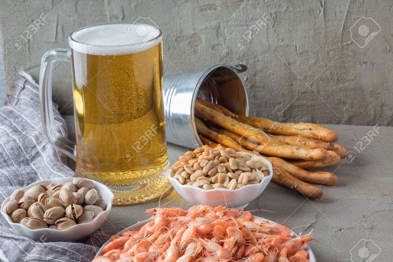 Mug Of Fresh Beer And Tasty Snacks On Grey Table Pint Of Alcohol Stock Photo Picture And Royalty Free Image Image 136287117