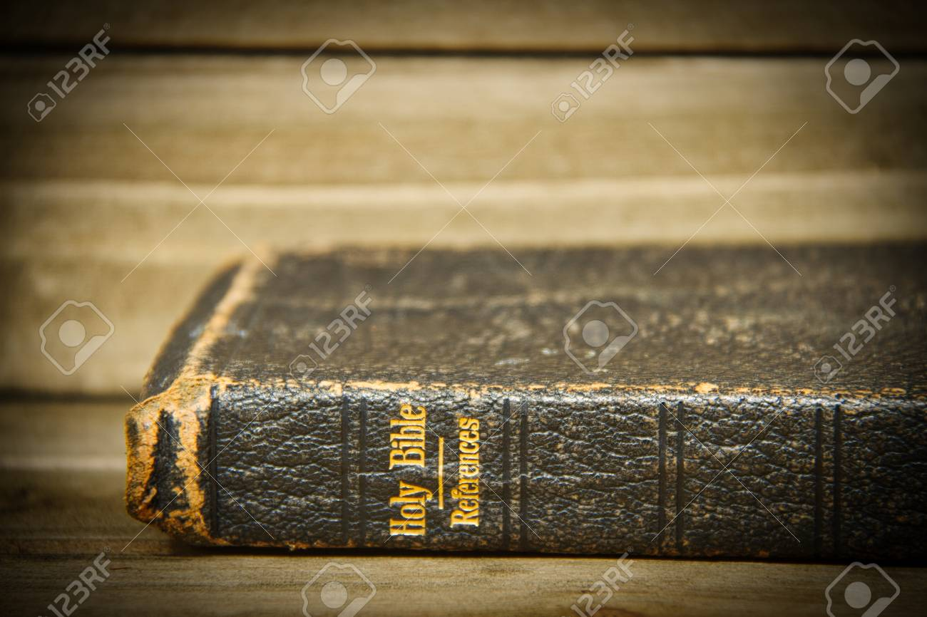 A Bible resting on its side on a wooden table with only the spine
