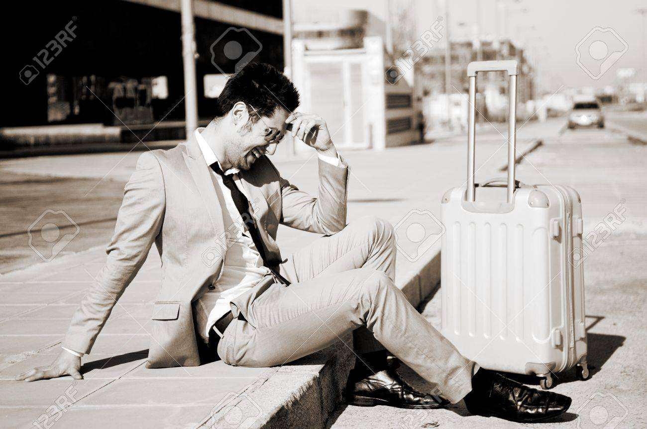 Man dressed in suit and suitcase sitting on the floor in the street Stock Photo - 16271812