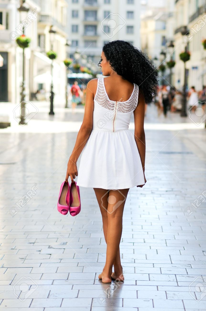 Portrait of a young black woman, afro hairstyle, walking barefoot on a commercial street Stock Photo - 16653407