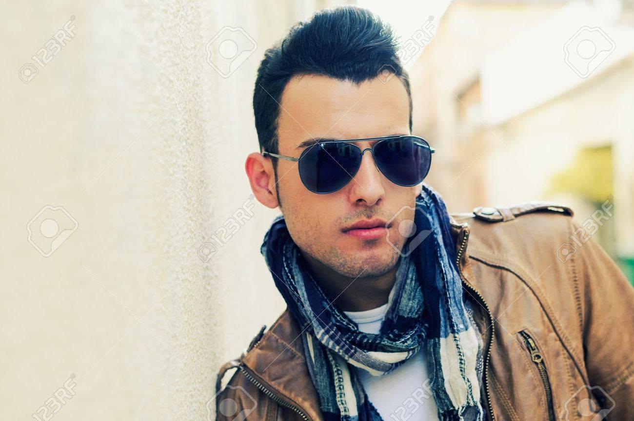 9a181672dcdaab Banque d images - Portrait d un jeune homme beau, modèle de mode, lunettes  de soleil teintées en milieu urbain