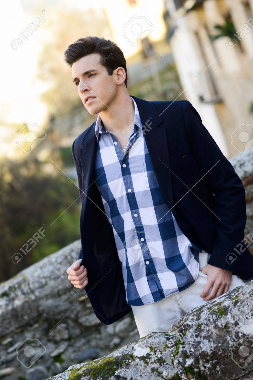 Portrait of handsome man with modern hairstyle smiling in urban background Stock Photo - 17803164