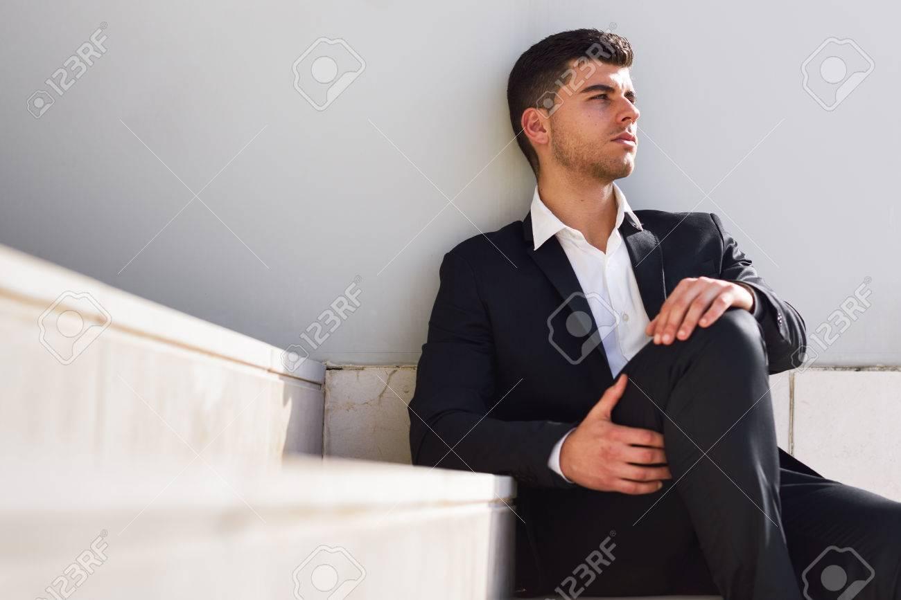 Jeune homme d'affaires près d'un immeuble de bureaux moderne portant le costume noir et chemise blanche assis sur le sol. Homme aux yeux bleus dans