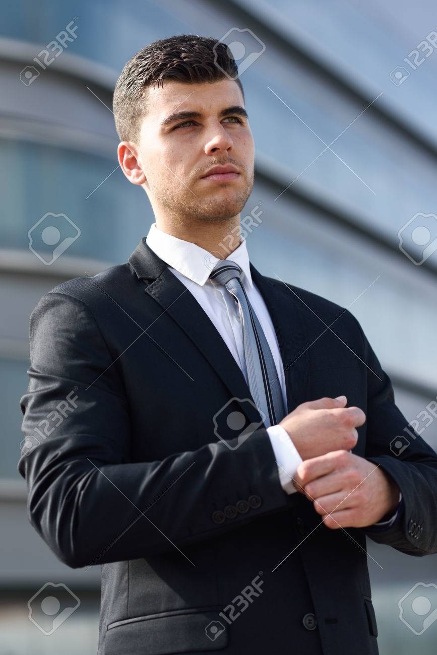 Jeune homme d'affaires près d'un immeuble de bureaux moderne portant le costume noir et cravate. Homme aux yeux bleus