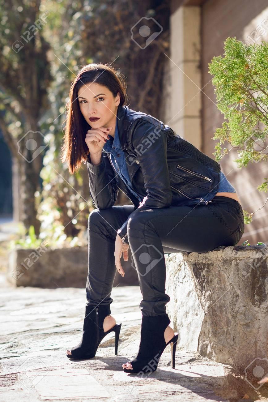 Belle jeune femme, sourire en arrière plan urbain. Fille portant veste en cuir et chemise bleue