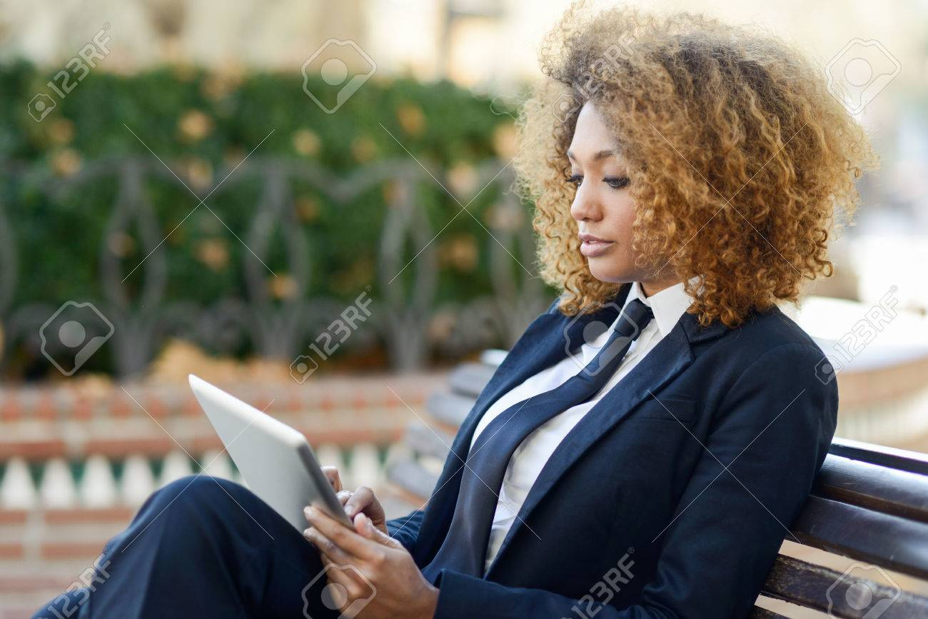 Beautiful black curly hair african woman using tablet computer on an urban bench. Businesswoman wearing suit with trousers and tie, afro hairstyle. - 55150666