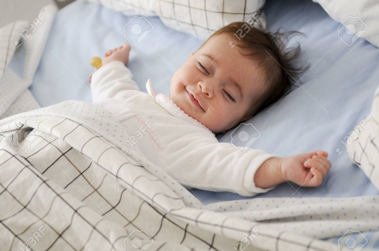 Smiling baby girl lying on a bed sleeping on blue sheets - 57170673
