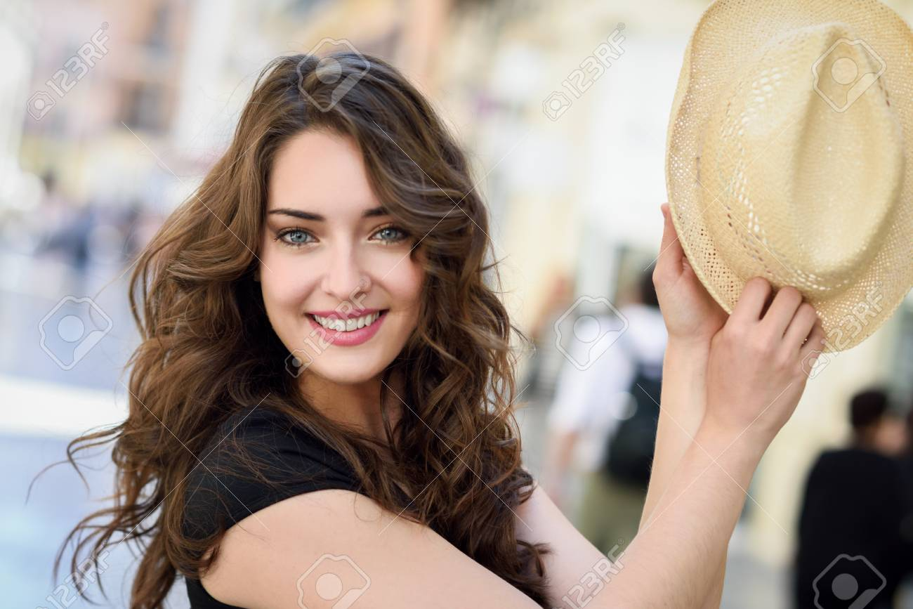 49b4f070ab4f Archivio Fotografico - Giovane donna felice con gli occhi azzurri che  sorride nella priorità bassa urbana. Ragazza che indossa vestiti estivi e  cappello da ...