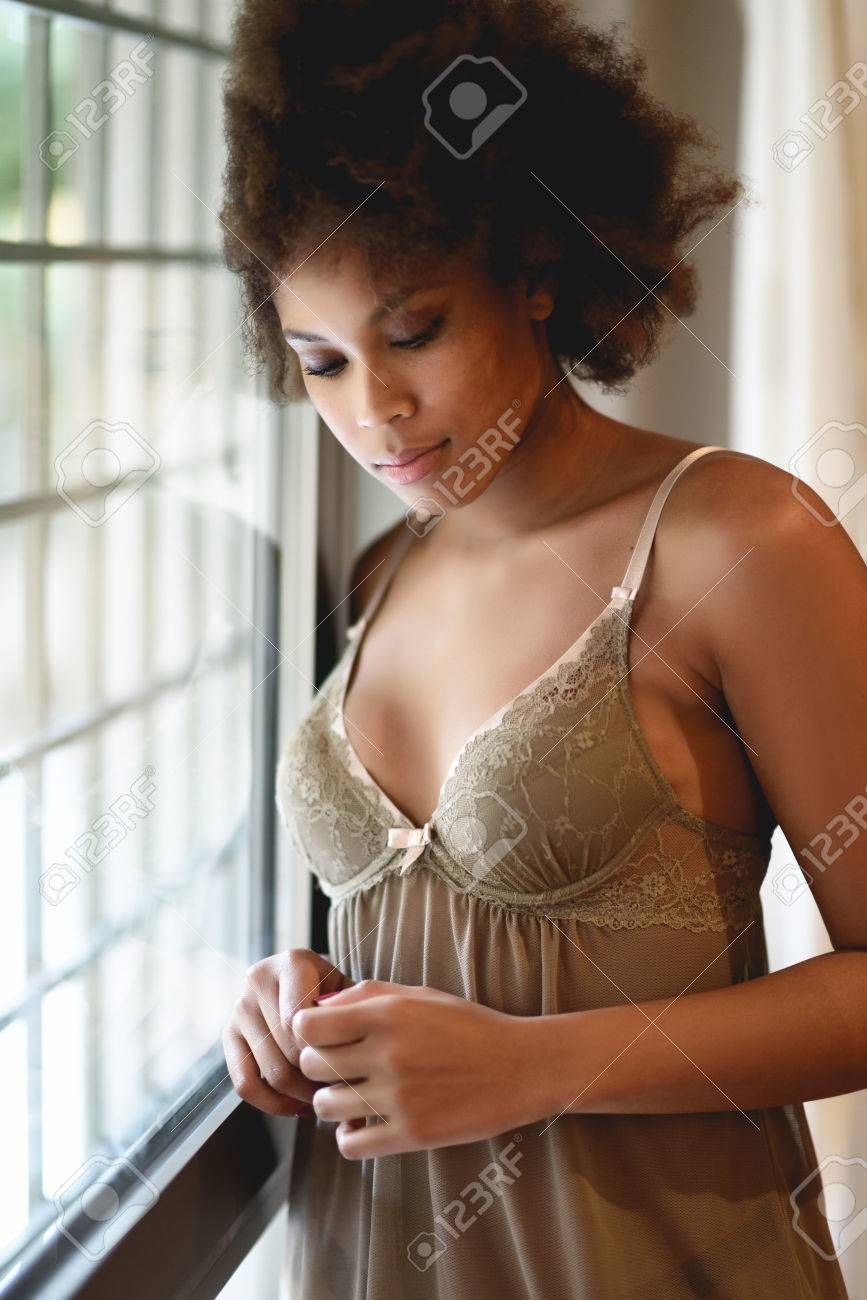 Stock Photo - Young black woman with afro hairstyle in lingerie near a  window. Mixed girl wearing underwear in her room with eyes closed. 17804b147