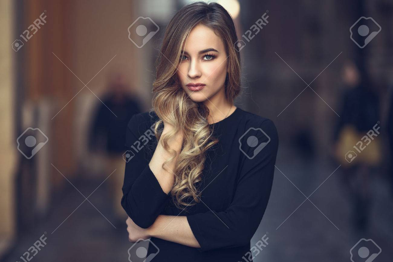 Blonde woman in urban background. Beautiful young girl wearing black elegant dress standing in the street. Pretty russian female with long wavy hair hairstyle and blue eyes. - 72165089