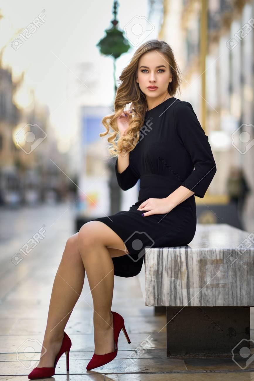02a19c026589 Blonde Frau im städtischen Hintergrund. Schöne junge Mädchen mit schwarzen  eleganten Kleid und roten High