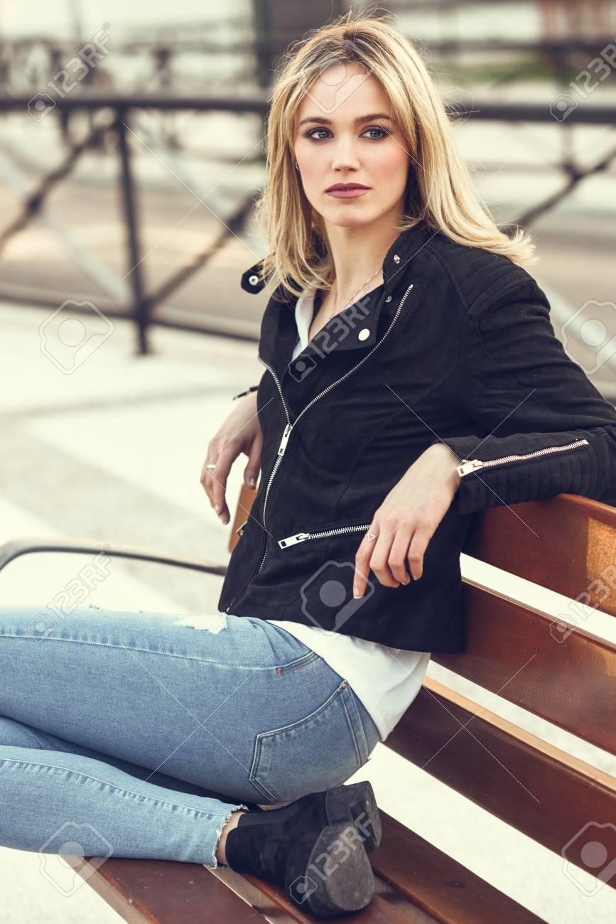 Belle Femme Blonde En Milieu Urbain. Jeune Fille Portant Une Veste à  Fermeture à Glissière Noire Et Un Pantalon En Jeans Bleu Assis Sur Un Banc  Dans La Rue. 3a25001b8fbf