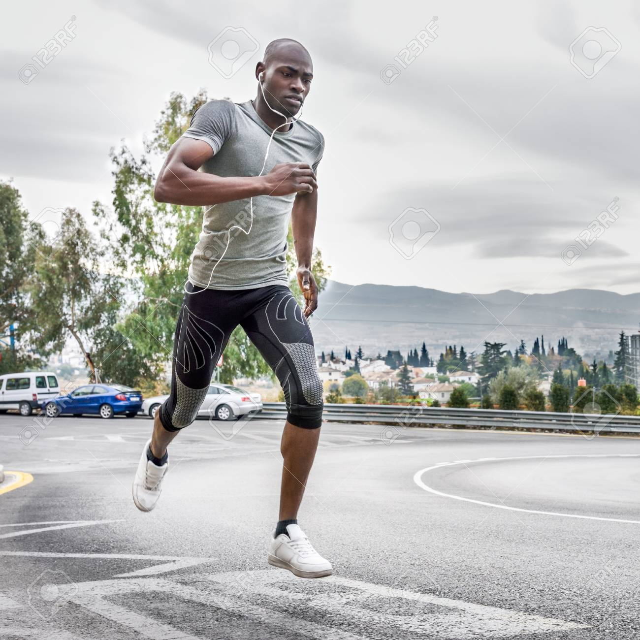 Noir courir en plein air dans la route urbaine écouter de la musique avec un casque blanc. Jeune homme exerçant avec scape de ville à l'arrière plan.