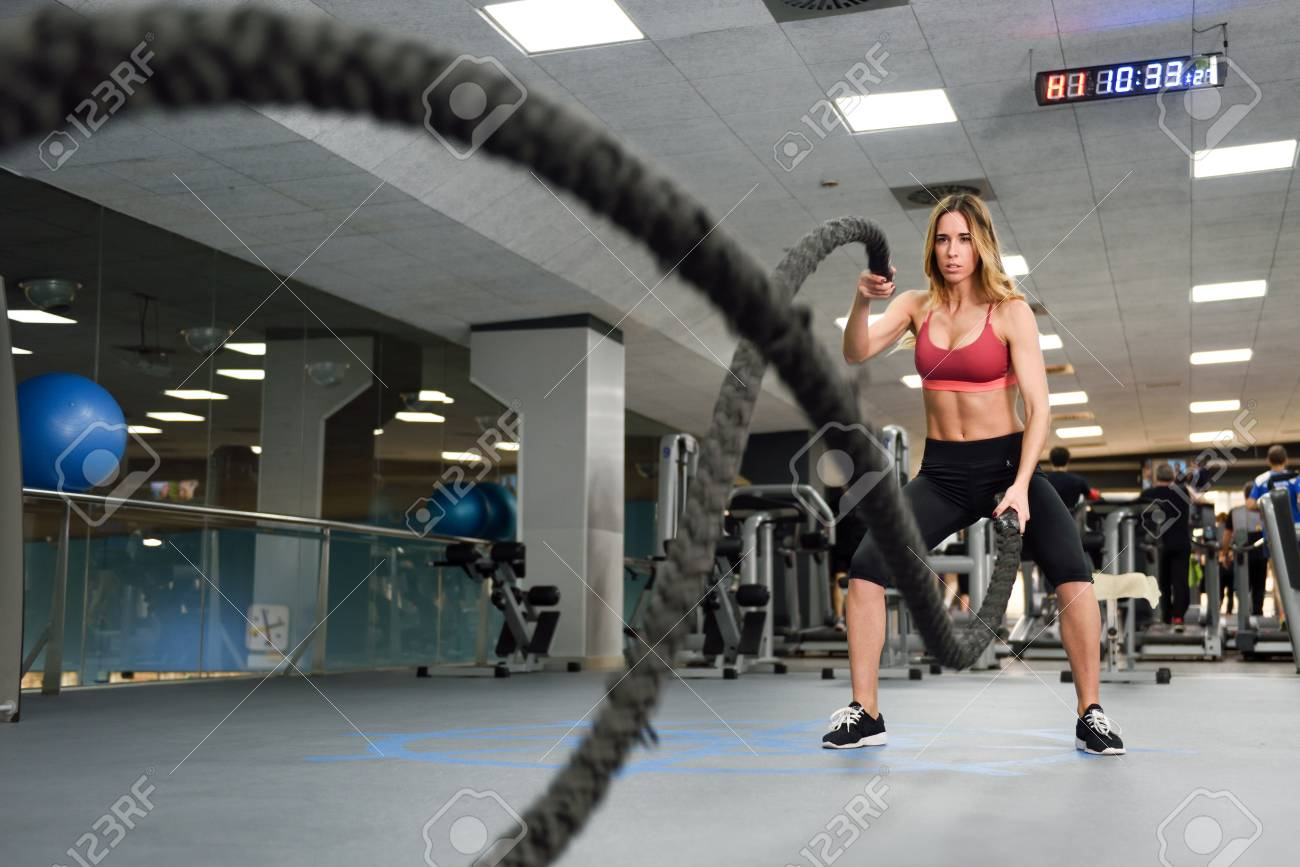Woman with battle ropes exercise in the fitness gym  Young female
