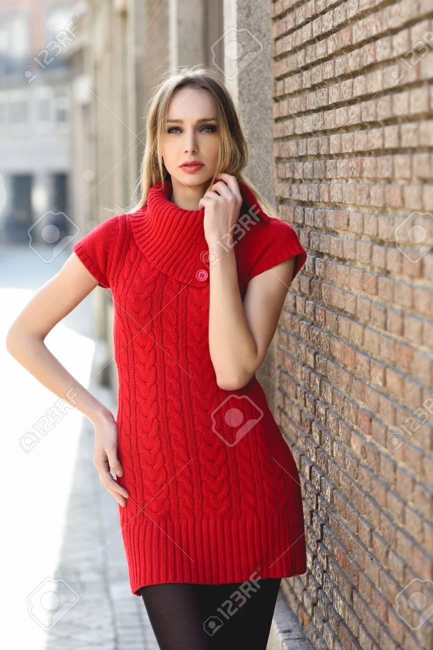 6e09d08ee11e Junge blonde Frau stand auf der Straße in der Nähe einer Mauer. Schöne  Mädchen in