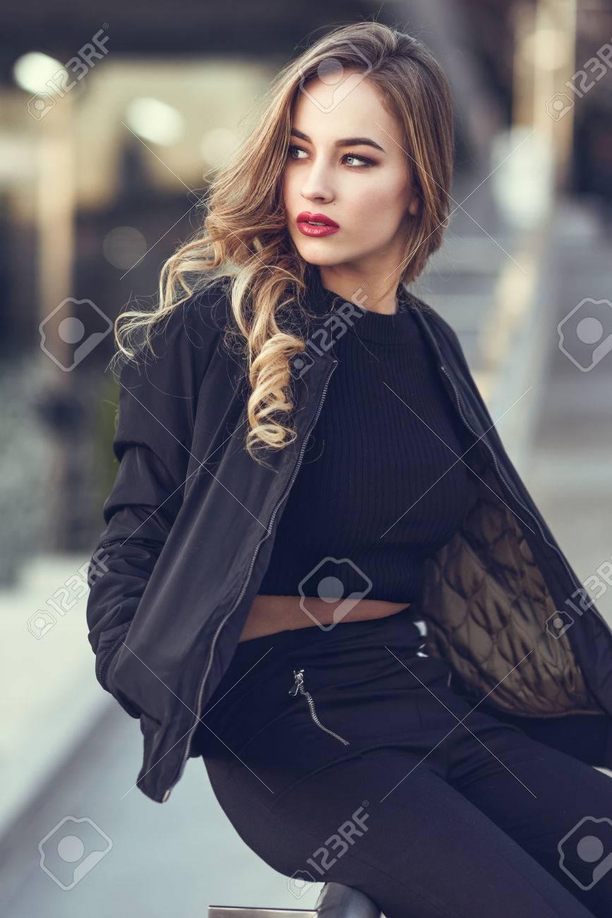 fcd492cc2 Mujer en fondo urbano. Joven rubia con hermosos ojos azules