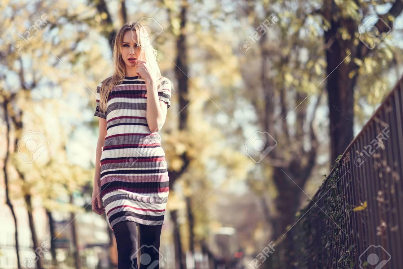 99e8ec81ec 88772028-young-blonde-woman-walking-in-the-street-beautiful-girl-in -urban-background-wearing-striped-dress-an.jpg