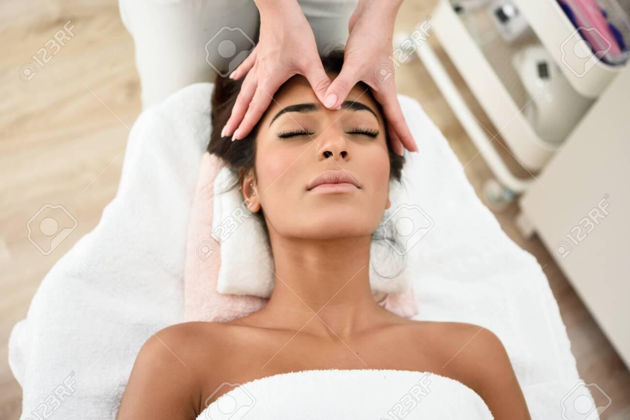 Woman receiving head massage in spa wellness center. - 122010063