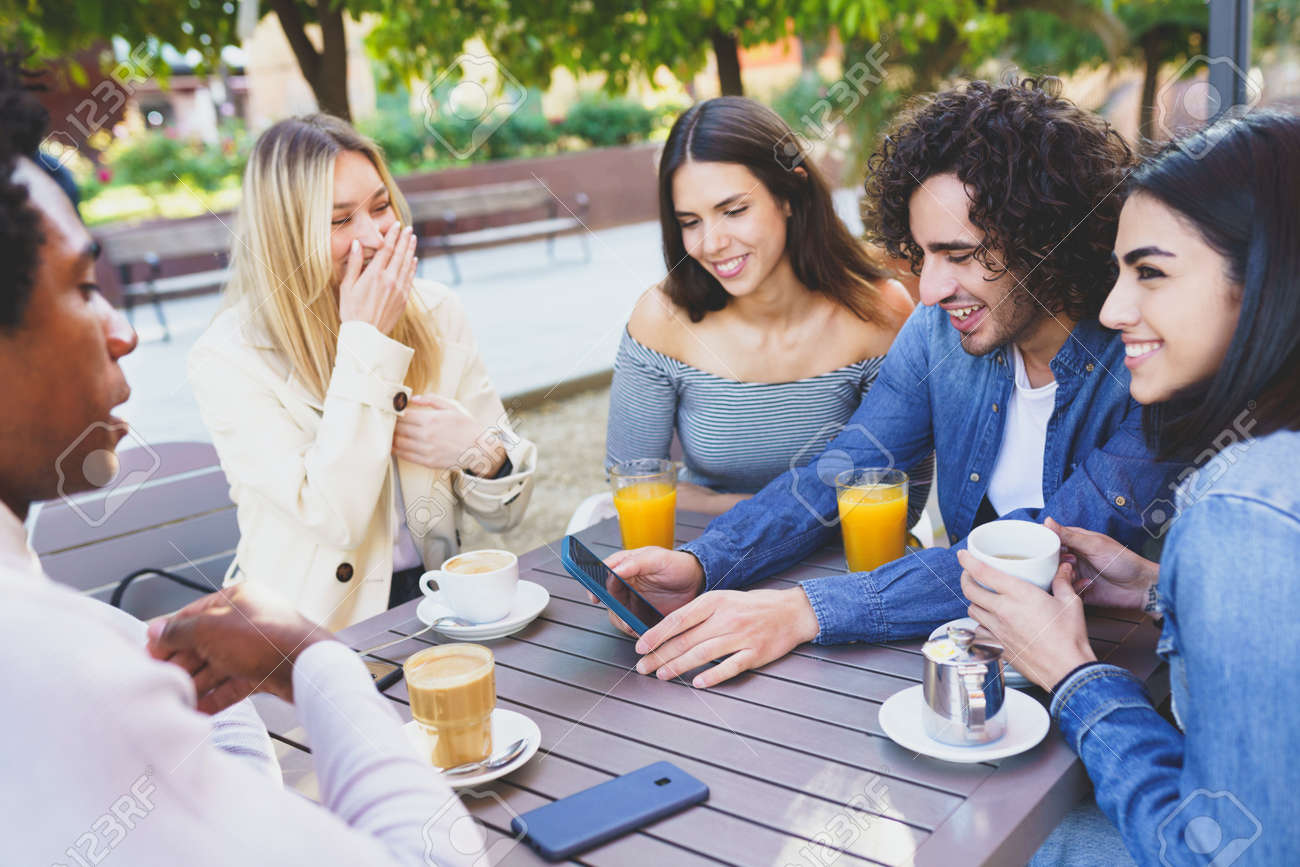 Multi-ethnic group of students having a drink on the terrace of a street bar. - 169787937