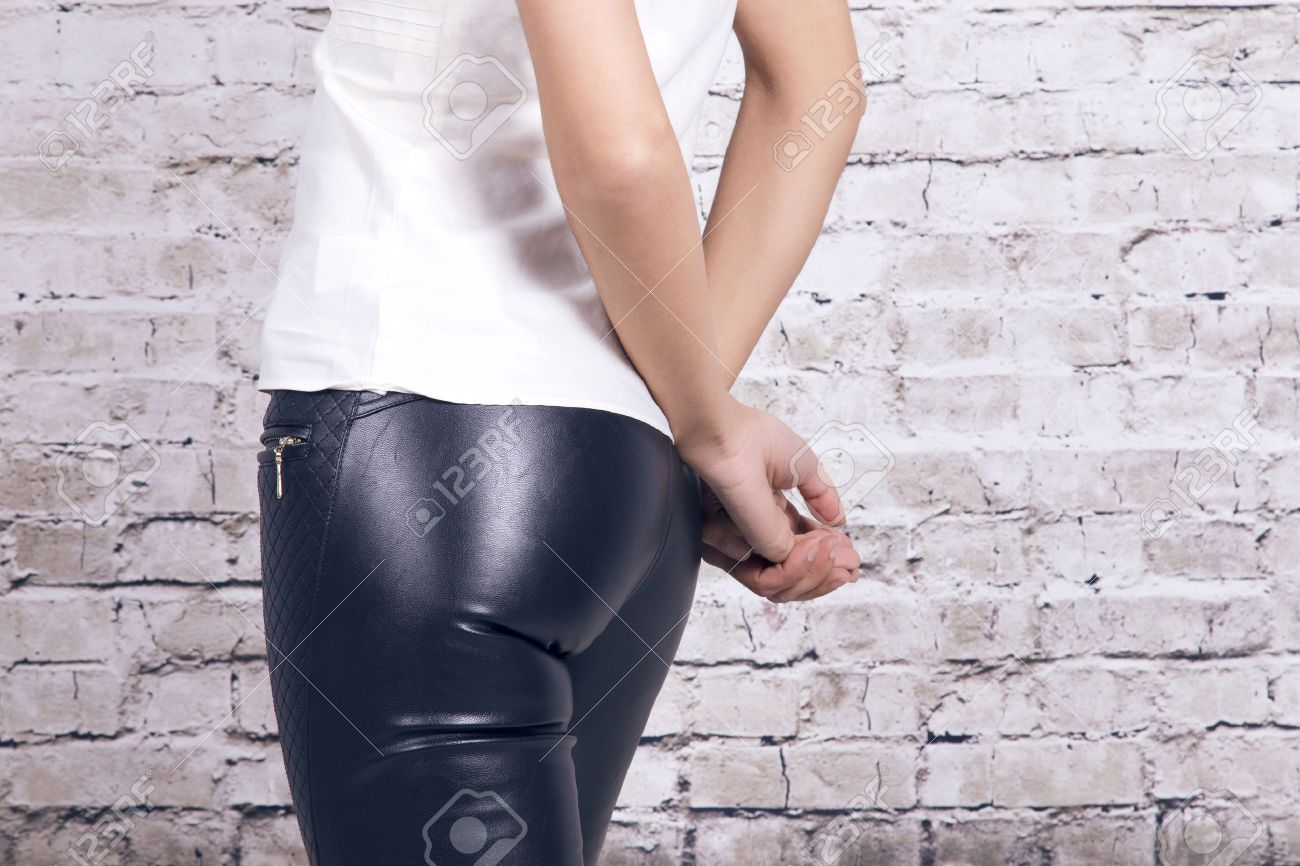 Back view of a woman wearing leather trousers and a white shirt, over a white brick wall. - 57913118