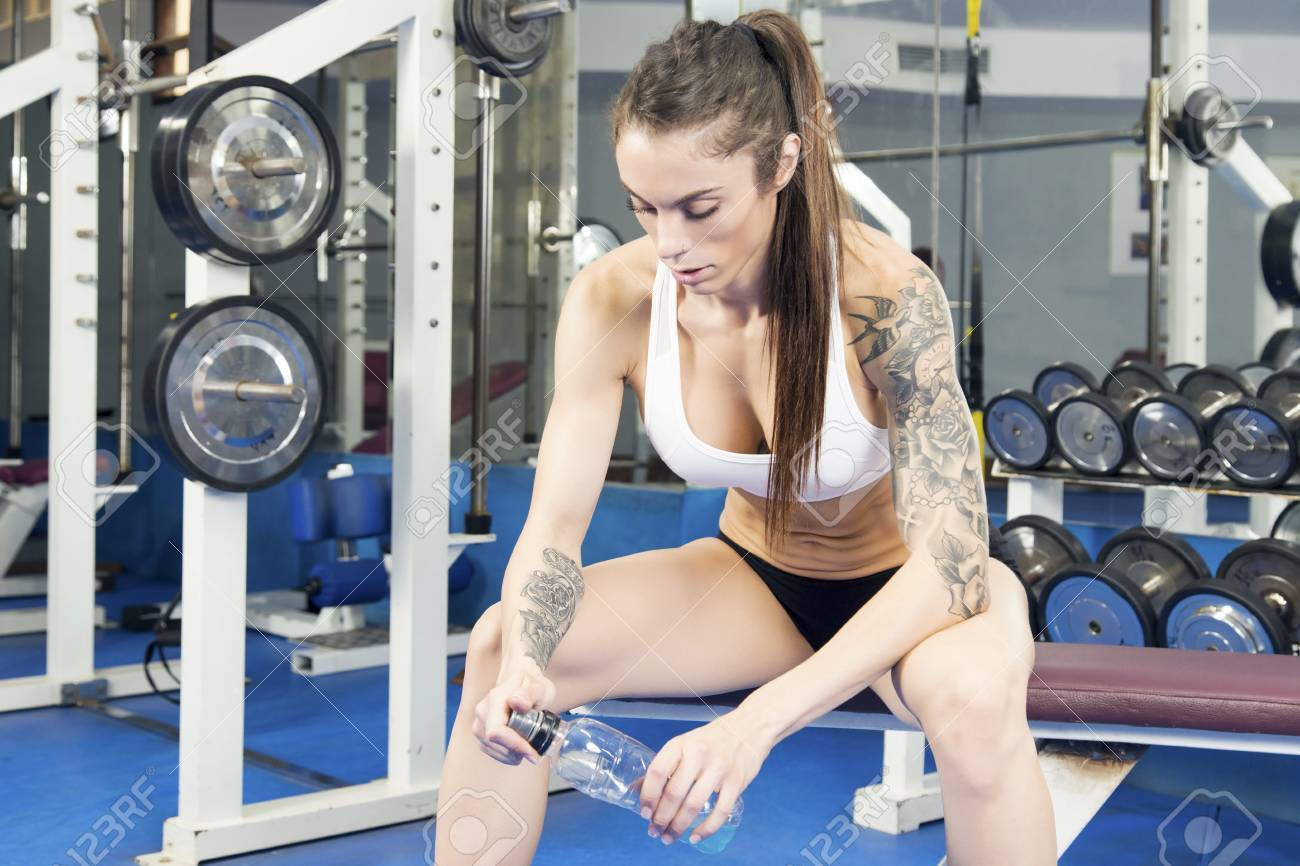 Woman sitting on a bench, at an old gym after her dumbbell workout,