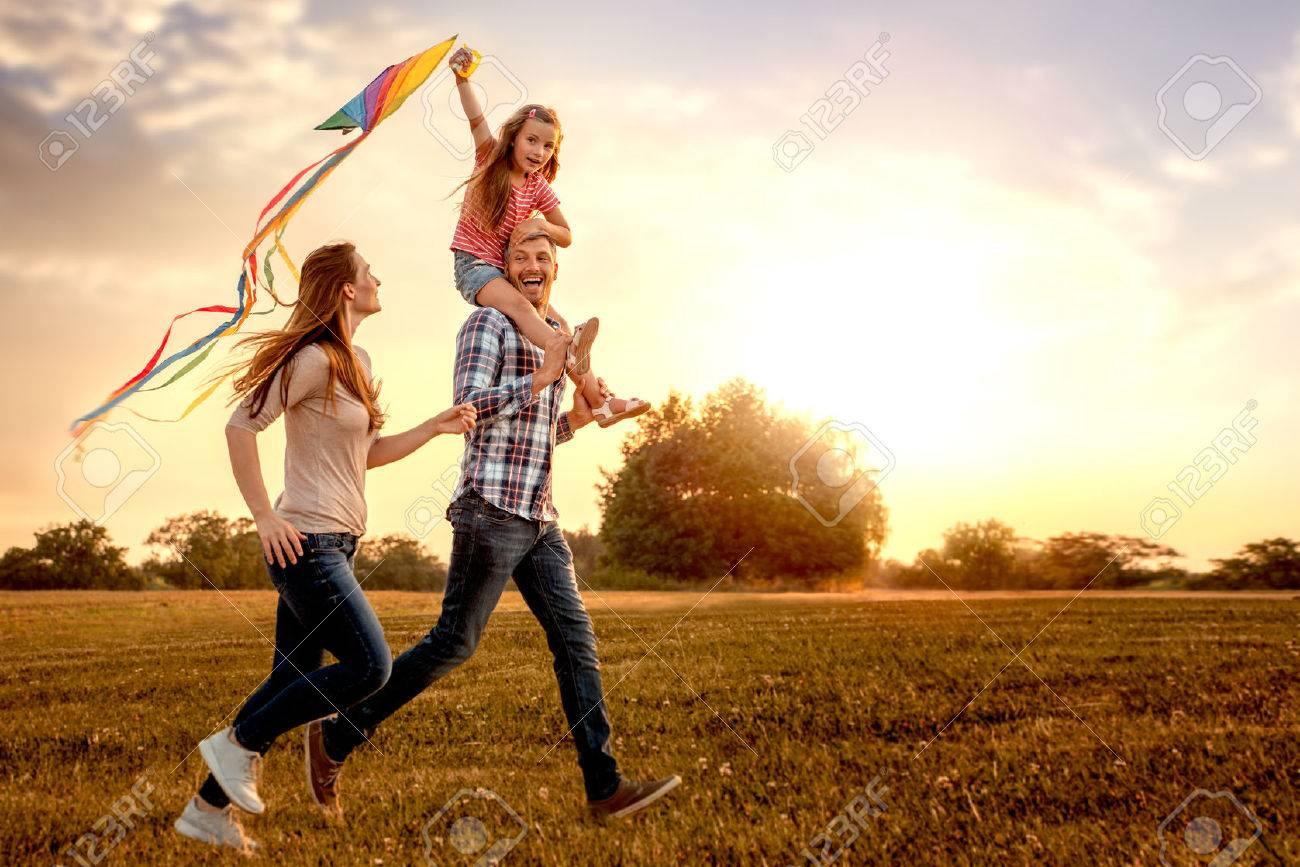 family running through field letting kite fly - 71296689