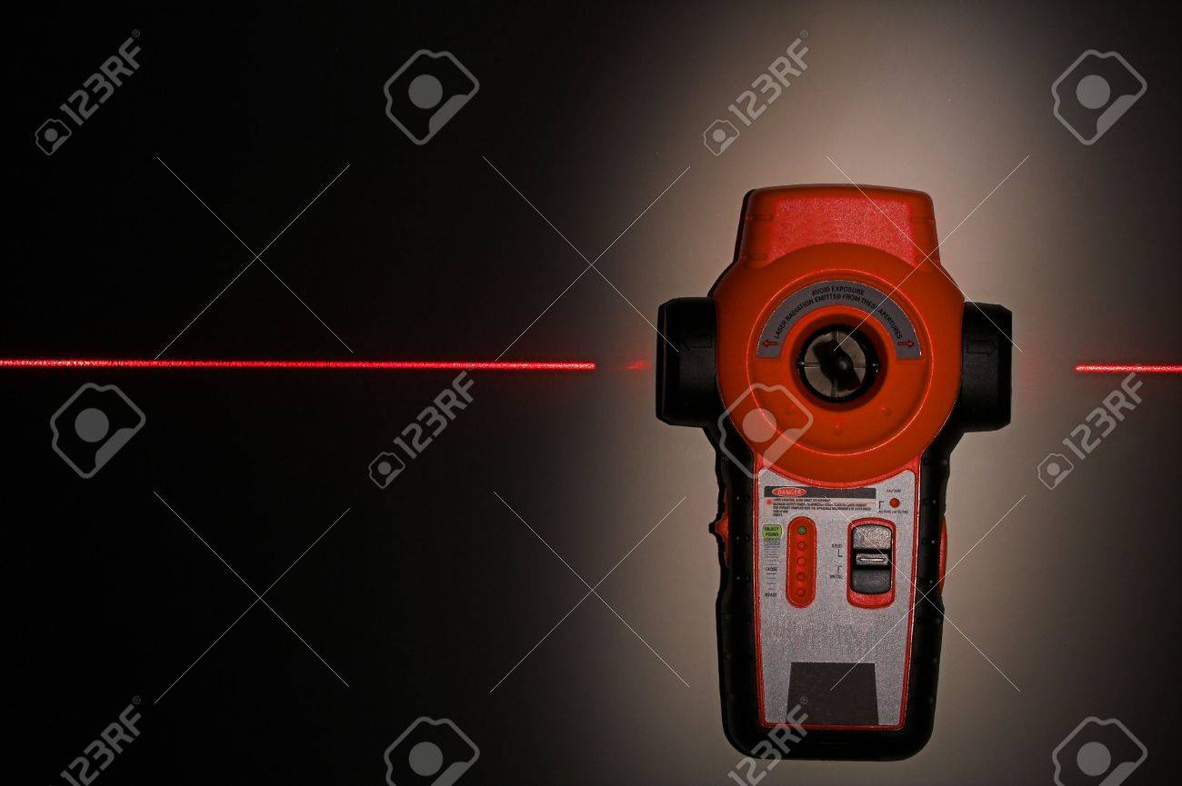 Laser Level Hanging On Wall With Laser Beam Black Background Stock