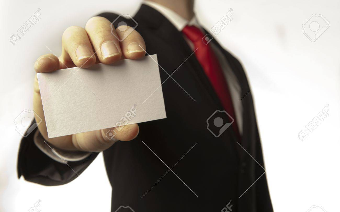 man in a suite and red tie holding a out a plain white business card for