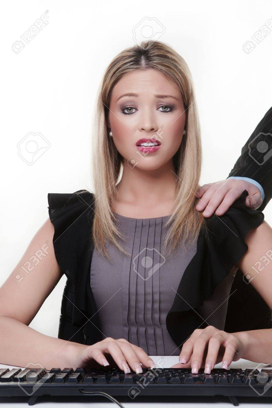 woman at her desk with a mans hand on her shoulder she not looking to happy is this sexual harassment Stock Photo - 13189449