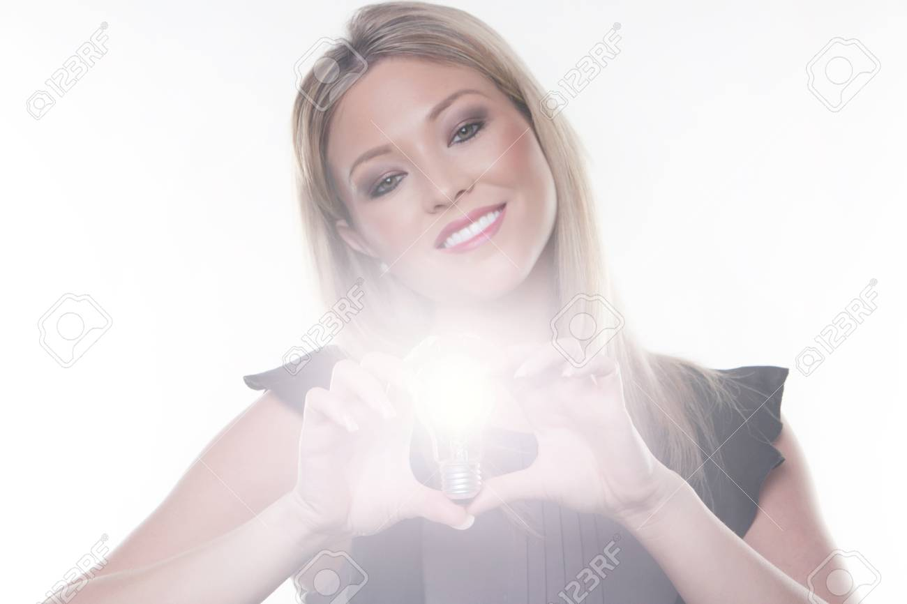 beautiful woman holding up a light bulbs in her hand with the bulb alight Stock Photo - 13330857