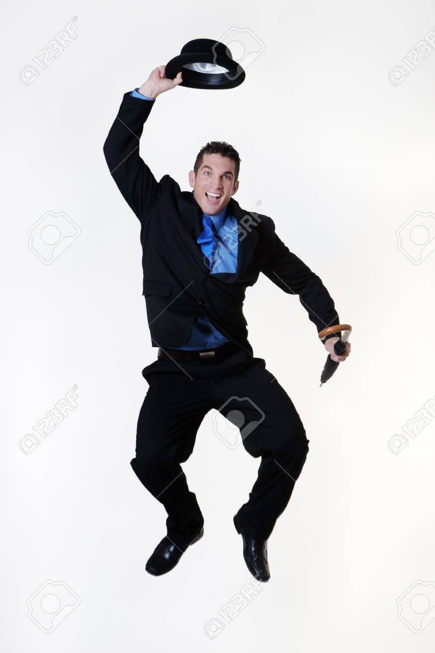 256d0c8ec35 man jumping in the air holding a bowler hat and umbrella Stock Photo -  15896748