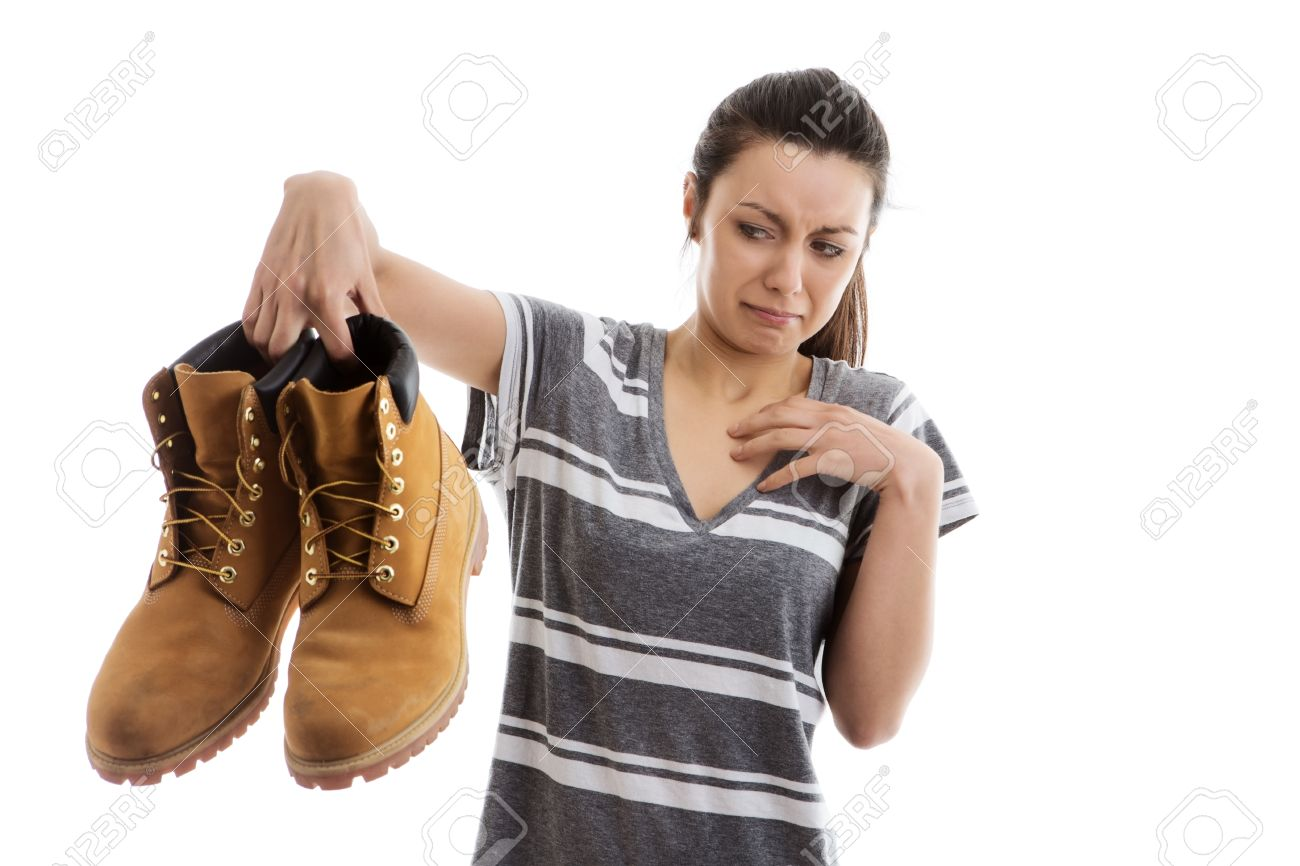Woman Holding A Pair Of Men Smelly Work Boots In The Air Not