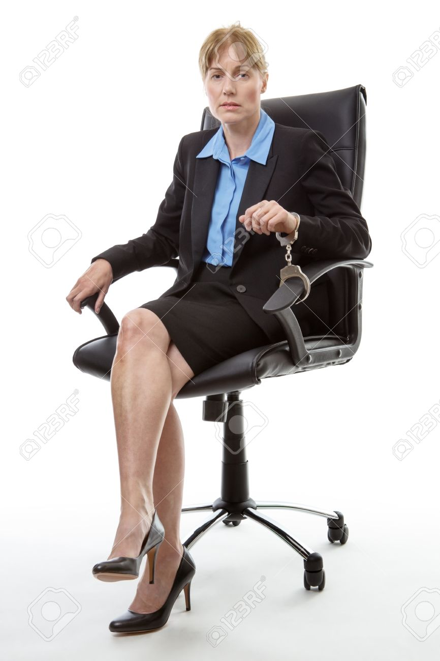 mature business woman sitting in an office chair handcuffed to