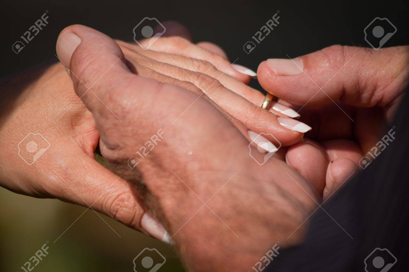 A closeup of a groom putting the ring on the brides finger during a wedding ceremony Stock Photo - 8276233