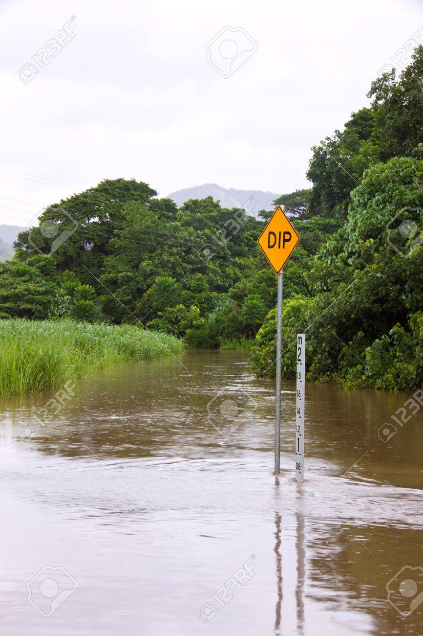 Flooded road with depth indicators and dip sign in Queensland, Australia Stock Photo - 8697774